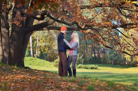 Happy couple relaxing in autumn park in good weather photo
