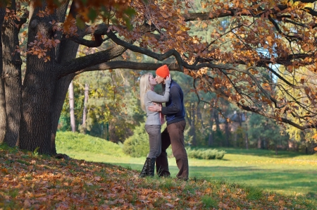 Happy couple kissing in autumn forest photo