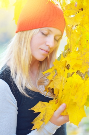 Blonde in an orange hat enjoying nature in the autumn park photo