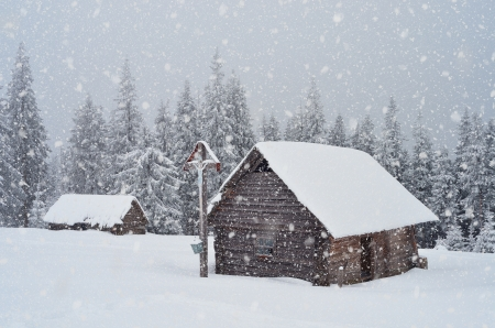 carpathian mountains: Winter landscape with a wooden hut in the mountains and the Orthodox cross  Ukraine, Carpathian Mountains