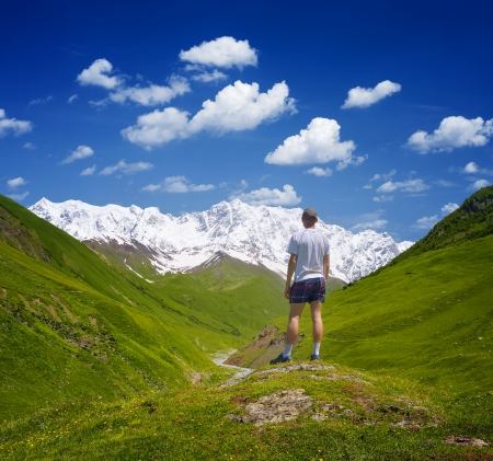 Guy is a tourist in the mountains of the Caucasus and looks at a snowy peak  Shkhara Mountain, Georgia photo