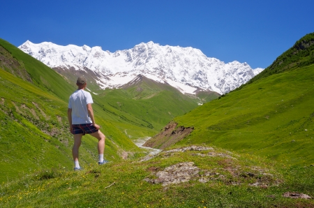 caucasus: Summer Landscape with a Man   tourist in the mountains of the Caucasus  Shkhara Mountain, Georgia, Caucasus Stock Photo
