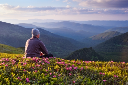 Summer landscape with a guy in a mountain valley  Red rhododendron flowers  Carpathians, Ukraine photo