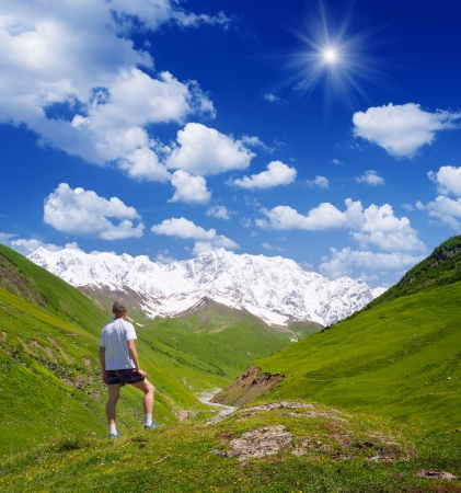 shkhara: Summer Landscape with a Man   tourist in the mountains of the Caucasus  Shkhara Mountain, Georgia, Caucasus Stock Photo