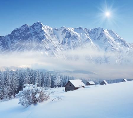 montañas nevadas: Paisaje de invierno en un valle de montaña con cabañas de los Cárpatos, Ucrania Foto de archivo
