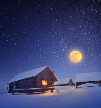 Winter landscape with a starry sky and the full moon  The light in the cabin in the mountains