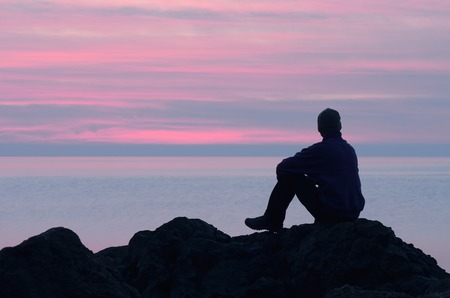Evening at the seaside  Guy sits on a rock by the sea and looking at sunset