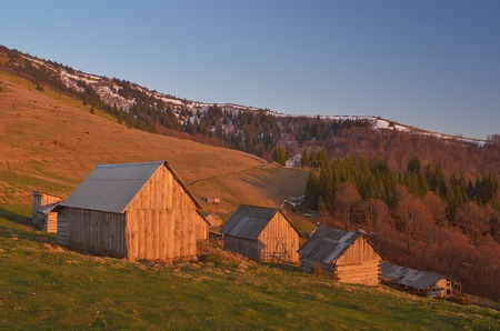 Spring landscape with wooden village of shepherds in the mountains  Light of the setting sun  Carpathian mountains, Ukraine, Europe photo