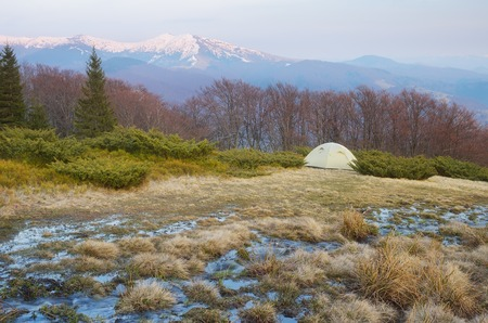 Spring landscape with tourist tent in the mountains  Mountain stream of melted snow  Carpathians, Ukraine, Europe photo