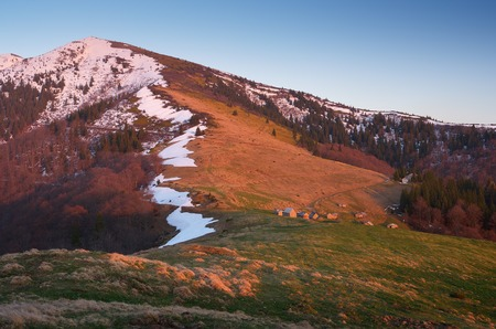 Spring landscape in the mountains  Evening light of the setting sun  Last snow on the mountain slopes  Carpathians, Ukraine, Europe photo