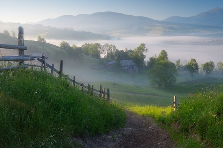 carpathian mountains: Morning landscape with a road in the mountain village  Sunny morning with fog over the settlement  Carpathian mountains, Ukraine, Europe