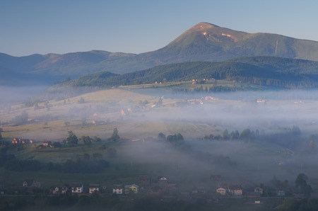 Misty morning in the mountains  View of the village under the fog  Carpathian mountains, Ukraine, Europe photo