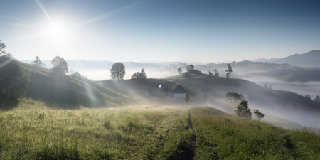 Panorama Mountain Village  Sunny morning with fog  Road in the grass leading to the house  Paradise  Carpathian mountains, Ukraine, Europe  photo