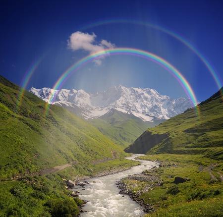alp: Summer landscape with river and rainbow in the mountains  Peak Shkhara Zemo Svaneti, Georgia  The main Caucasian ridge