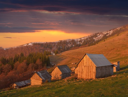 Spring landscape with wooden village of shepherds in the mountains  Light of the setting sun