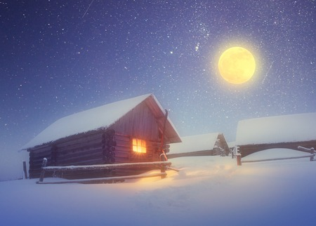 full moon effect: Winter landscape with a starry sky and the full moon  The light in the cabin in the mountains  Soft effect  Color toning