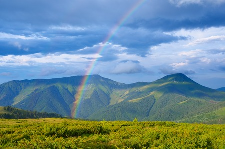 Summer landscape with a rainbow in the mountains  Sunshine after the rain  Beauty in nature 스톡 콘텐츠
