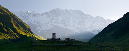 Panorama Caucasus Mountains  Stone medieval church in a mountain valley  View of Mount Shhara  Ushguli community, Zemo Svaneti, Georgia photo