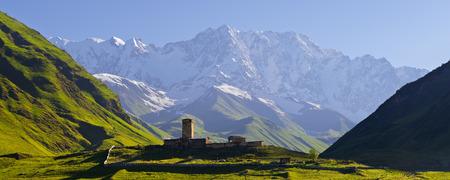svan: Panorama Caucasus Mountains  Stone medieval church in a mountain valley  View of Mount Shhara  Ushguli community, Zemo Svaneti, Georgia