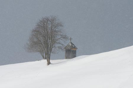 Winter landscape with a chapel near the tree  Snowfall in mountain village  Mountains Carpathians, Ukraine, Europe photo