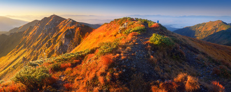 First rays of the sun on the mountain slopes  Panoramic landscape of the ridge with a footpath photo