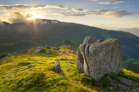 Summer landscape in the mountains with the sun hiding around the ridge photo