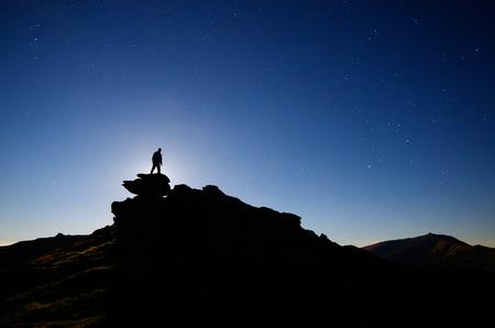luz de luna: Paisaje de la noche con el cielo estrellado Claro de luna sobre un hombre de pie sobre una roca