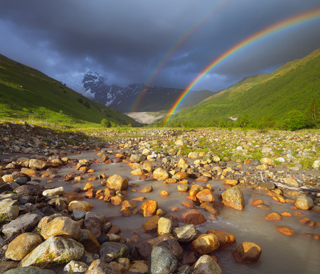 Summer landscape with a rainbow in the mountains above the river  Zemo Svaneti, Georgia Stok Fotoğraf