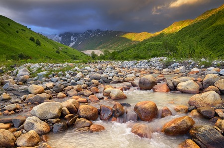 Summer landscape with the mountain river  Black clouds over a mountain valley  Zemo Svaneti, Georgia photo