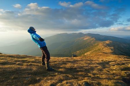 男のバランスをとる強い風が山の秋の風景
