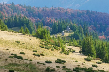 Autumn landscape with old wooden church in the mountains photo