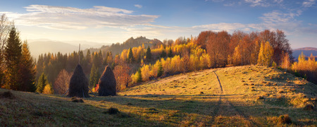 Autumn landscape with haystacks. Evening in a mountain village. Carpathian mountains, Ukraine, Europe photo