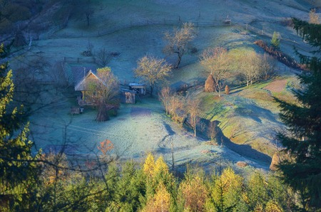Autumn landscape. Farmstead with wooden houses. Morning with frost. Carpathian mountains, Ukraine, Europe photo
