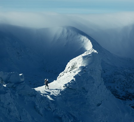 Winter landscape. Sunny day in the mountains. Tourist standing on a rock Archivio Fotografico