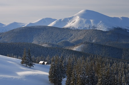 Fabulous view of wooden houses in the mountains. Christmas landscape. Carpathians, Ukraine, Europe photo