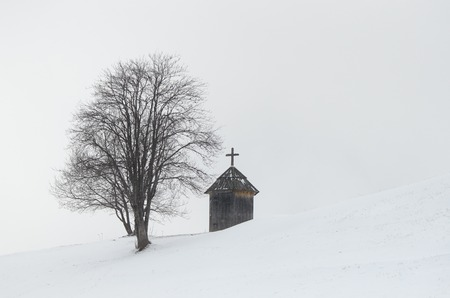 Winter landscape. Wooden chapel and a tree on a hill. The village is in the mountains. Carpathians, Ukraine, Europe photo