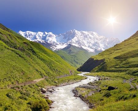 svan: Paesaggio estivo con il fiume e la montagna di neve. Peak Shkhara Zemo Svaneti, Georgia. La cresta principale sorride