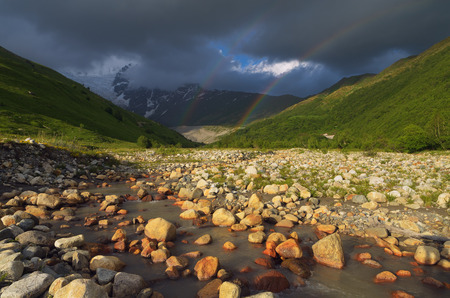 Summer landscape with a rainbow in the mountains. Beauty in nature photo
