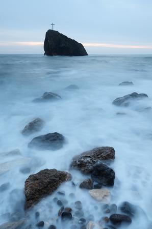 mystery of faith: Cross on the rock. Sea landscape