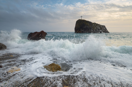 Storm sea with beautiful waves. Seascape with a rock. Christian cross on the cliff. Cloudy day, the bad weather. Crimea