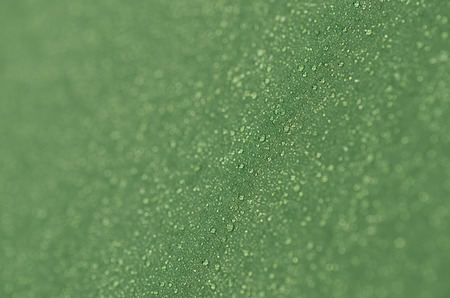 waterproofing material: Drops of morning dew on a tourist tent. Abstract background of green fabric. Shallow depth of field