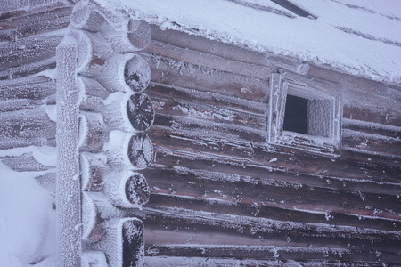 wooden color: Old wooden house in the frost. Abandoned mountain village. Color toning. Low contrast