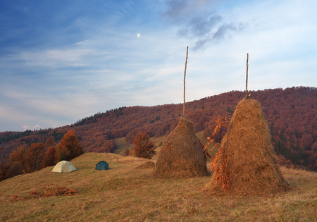 autumn landscape: Tourist camping in the mountain village. Autumn landscape. Haystacks on the meadow