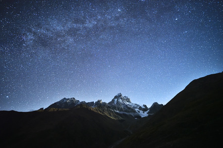 peak: Night landscape. Starry sky with the Milky Way over the mountains. Mount Ushba in the light of the rising moon. Main Caucasian ridge. Zemo Svaneti, Georgia Stock Photo