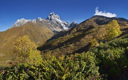 svaneti: Autumn landscape. The mountain panorama. Sunny day. Mount Ushba, Main Caucasian ridge. Zemo Svaneti, Georgia Stock Photo