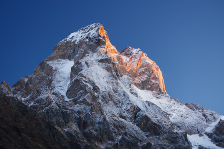 svaneti: Mountain top at sunrise. Mount Ushba, Svaneti, Georgia, Caucasus. The first rays of the sun. Beauty in nature