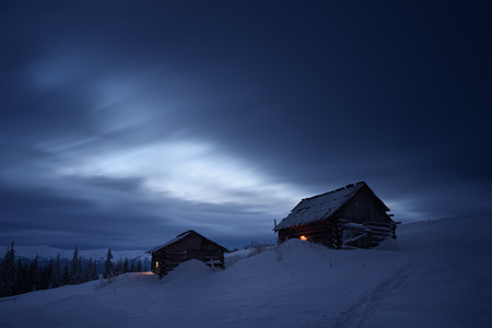 Night landscape in the mountains. Two wooden houses in the mountain settlement. Light in the windows. Path in the snow. Cloudy sky. Carpathians, Ukraine, Europe