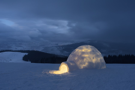 igloo: Snow igloo. Winter in the mountains. Evening Landscape with shelter for extreme tourists. Adventure Outdoors Stock Photo