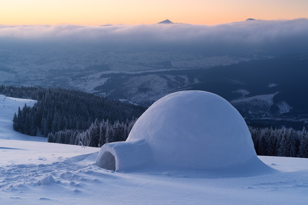 Snow igloo on a mountain hill. Winter landscape. Adventures in the winter campaign 스톡 콘텐츠