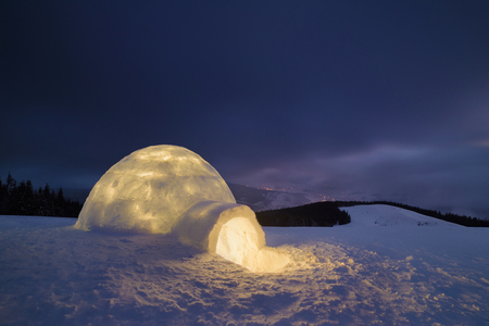 Night in the mountains. Snow igloo with light. Extreme housing. Carpathians, Ukraine, Europe